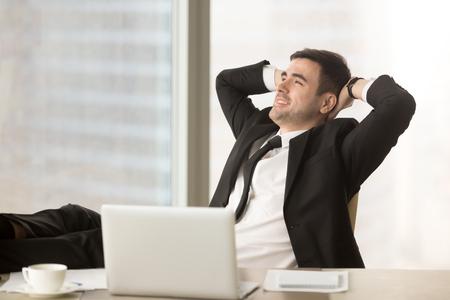 Gelukkige ontspannen zakenman rustende handen achter hoofd dichtbij PC-laptop weg kijkend zittend bij bureau met voeten omhoog op lijst, gebeëindigd werk, gedaane baan, voltooide alle taken, ontspannend na harde werkdag