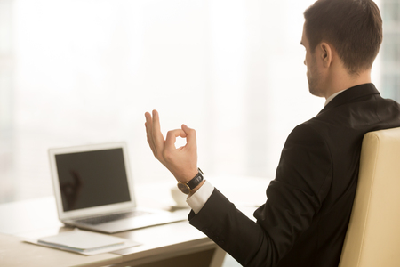 Close up of hand in chin mudra yogic gesture, mindful calm yogi businessman meditating at workplace near laptop, doing yoga exercise, practicing breathing, meditation at work, no stress, back view Stock Photo - 84440007