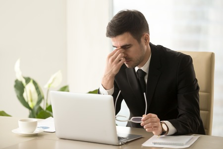 Exhausted tired businessman working on laptop at office, massaging nose bridge, holding glasses, feeling fatigue discomfort, eye strain after long wearing spectacles, eyesight problem, need eye drops Stock Photo