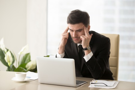Serious frustrated businessman with closed eyes suffering from headache migraine at workplace, massaging temples, feeling tired exhausted, chronic work stress, tries to remember important information