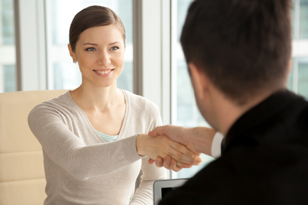 Smiling beautiful woman shaking male hand, greeting handshake of female applicant arriving at job interview, businesswoman making good first impression at meeting with new partner, women in business Stockfoto