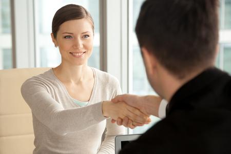 Glimlachende mooie vrouw mannelijke hand schudden, groet handdruk van vrouwelijke aanvrager aankomen op sollicitatiegesprek, zakenvrouw goede eerste indruk op ontmoeting met nieuwe partner, vrouwen in het bedrijfsleven maken Stockfoto