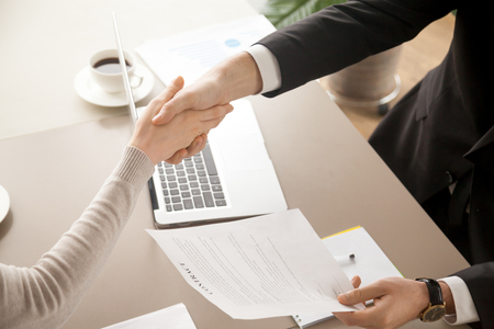 Close up top view of business handshake, male and female hands shaking over office desk after signing contract, holding signed statement, sealing deal as good result of successful negotiations Stok Fotoğraf