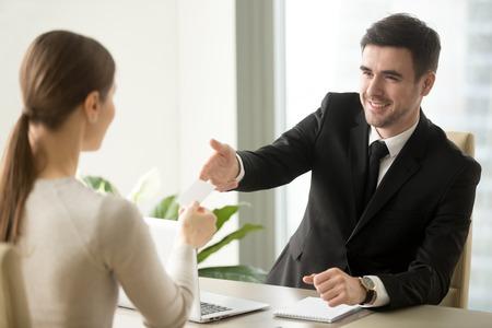 Vriendelijke succesvolle zakenman die visitekaartje geeft aan onderneemster op kantoor tijdens eerste vergadering met geinteresseerde cliënt, die pasteboard, persoonlijke informatie aanbiedt, me roept, contacteert ons