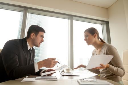 Zijaanzicht van collega's die ruzie maken op het werk, leidinggevenden het oneens zijn over de documenten, fouten in het contract hebben gevonden, fouten bij het papierwerk, zakelijke partners die claims hebben op documenten, betwisten over een overeenkomst Stockfoto