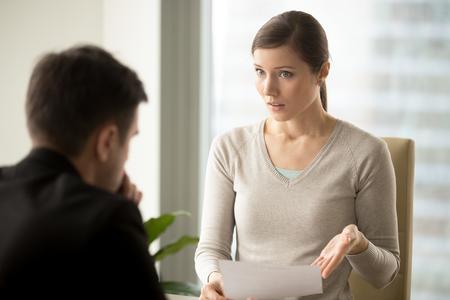 Femme d'affaires irritée tenant un document, en désaccord avec les termes du contrat, refuse de signer le document, pose des questions sur les conditions de l'accord, le patron n'est pas satisfait du rapport ou du résultat du travail Banque d'images