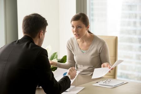 Verärgerte Geschäftsfrau, die mit Geschäftsmann über Schreibarbeitsausfall am Arbeitsplatz, die Führungskräfte, die Konflikt über Verantwortung für schlechte Arbeitsergebnisse haben, Ergebnisse streiten, Partner, die über Vertrag während des Treffens streiten