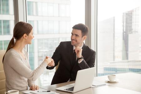 Glimlachende onderneemster en zakenmanhandenschudden, inleiding en kennismaking, die goede indruk maken bij eerste vergadering, die nieuwe huurwerknemer welkom heten, handen schudden als groetgebaar
