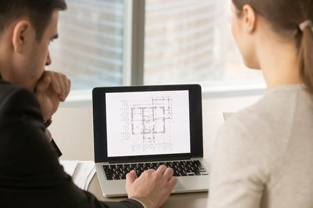 Vista trasera en los arquitectos mirando la pantalla de la PC mientras trabajaba con una copia escaneada del plan de construcción, la estimación del valor de la propiedad, la evaluación inmobiliaria, la inversión en la construcción, de cerca, se centran en la computadora portátil Foto de archivo - 84440056