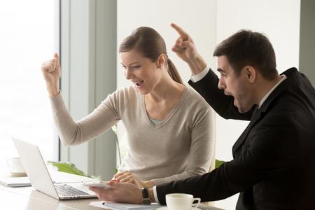 Euforisch blij zakenmensen verbaasd over grote winsten, kijkend naar laptop scherm, juichend ondersteunend tijdens het kijken naar uitzending, winnaars vieren zakelijk succes, online veiling, veel geluk, goed resultaat