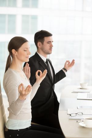Relajado hombre de negocios consciente y empresaria meditando en el trabajo con los ojos cerrados, gesto yoga mudra de la barbilla, empleados tranquilos haciendo ejercicios de respiración, meditación corporativa, yoga de oficina, mantener la calma