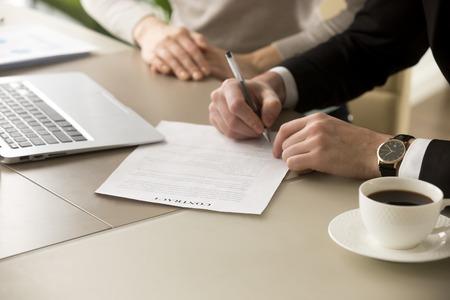 Zakenman in pak zet handtekening op contract op zakelijke bijeenkomst na onderhandelingen met zakenvrouw, mannelijke hand ondertekent officieel document, ondertekent naam op wettelijke bindende overeenkomst, close-up weergave
