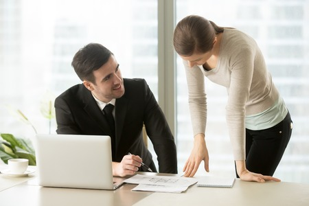 Businessman and businesswoman negotiate over building plan, architects work on house construction project, real estate agents discuss layout at office desk, property value estimation, home appraisal Stock Photo