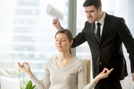 Calm attractive businesswoman practicing yoga at work, meditating in office with eyes closed, ignoring angry bad boss standing behind her back, avoiding negative people, positive thinking, no stress Stock Photo
