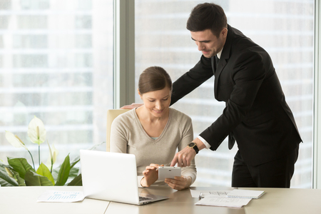 Happy architects using digital tablet in office, management team discussing planning new building project, smiling estate agents monitoring property market with mobile application for house hunting Stock Photo