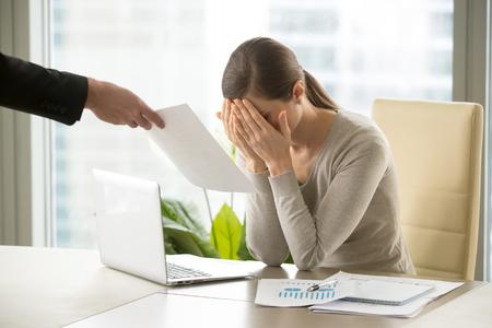 Une main masculine donne un document de femme d'affaires triste et déprimée avec de mauvaises nouvelles, un entrepreneur désespéré contrarié reçoit un avis de licenciement, se cachant le visage en pleurs, frustré par la faillite, l'échec d'une entreprise ou d'être renvoyé Banque d'images - 84440090