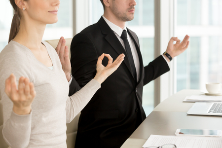 Close up view of business people meditating at desk, practicing pranayama technique to relax at office, holding hands in chin mudra gesture, corporate yoga, stress management for workspace wellness Stock Photo - 84440129