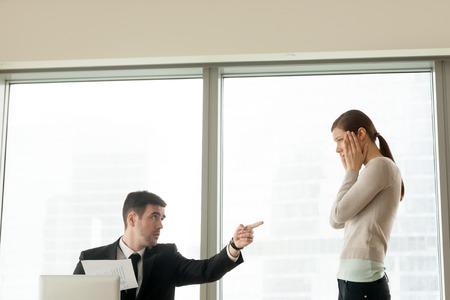 Slechte ceo schiet incompetente stagiair op voor slecht resultaat, boze baas verwerpt ineffectieve medewerker, incompetentie als reden om ontslagen te worden, discriminatie op het werk op het werk, kopie ruimte Stockfoto