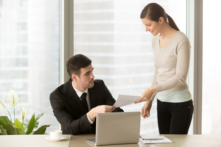 Young smiling personal assistant giving document to boss in his office, female accountant reporting great work to ceo, junior manager showing to executive increased financials, project stats on paper