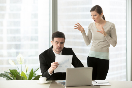 Female disrespectful employee grimacing standing behind back of serious executive checking report with bad work result, impolite young subordinate making funny scary face as if shouting at boss