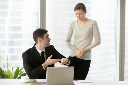 Gereizter Chef, der auf Armbanduhr zeigt, unzufriedener CEO, der Erklärungen von weiblichem Manager verlangt, nervöser Angestellter, der Entschuldigungen für versäumte Frist macht, Praktikant entschuldigt sich für verspätet und kommt spät Standard-Bild