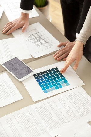 Interior designers or design professionals working with color swatches palette and house layout at office desk, decorators choosing shade of blue to offer client for home refurbishment, close up view
