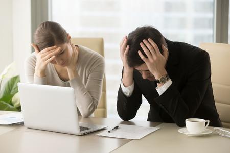 Moe gefrustreerde zakenmensen voelen gestresst, verstoren executives zitten in de buurt van laptop, houden hoofd in handen, zorgen over mislukken van zakelijke problemen, gedeprimeerd door slecht nieuws, faillissement van het bedrijf Stockfoto