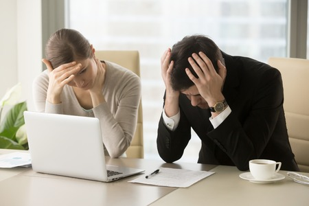 Tired frustrated business people feeling stressed, upset executives sitting near laptop, holding head in hands, worried about business problem failure, depressed by bad news, company bankruptcy Stok Fotoğraf - 84510598