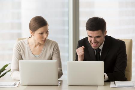 Boos werknemer verliezer kijkt jaloers op gepromoveerde collega-winnaar geniet van succes, goed nieuws tijdens het werken op laptop, voelt zich jaloers op rivalen prestaties, team rivaliteit, oneerlijke concurrentie