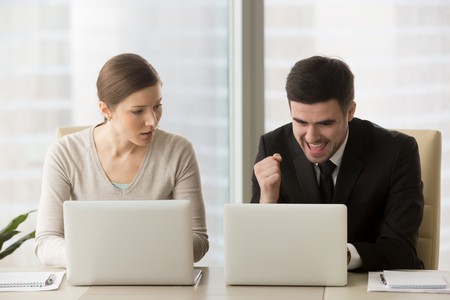 Resentful employee loser looks enviously at promoted colleague winner enjoying success, good news while working on laptop, feels jealous about rivals achievements, team rivalry, unfair competition