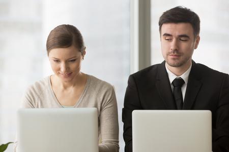 Neugierig neugierig Geschäftsmann mit schlechten Manieren schaut Blick auf Laptop-Bildschirm der Geschäftsfrau versucht, Idee des Mitbewerbers zu stehlen, Kopieren der Arbeit bei der Unternehmensprüfung, Sammeln von Informationen über Rivalen Standard-Bild