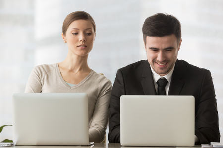 Interested curious corporate spy looking at colleagues laptop, spying on rival, cheating on examination, stealing idea, sneaking peek, taking inquisitive glance at computer screen of unaware coworker