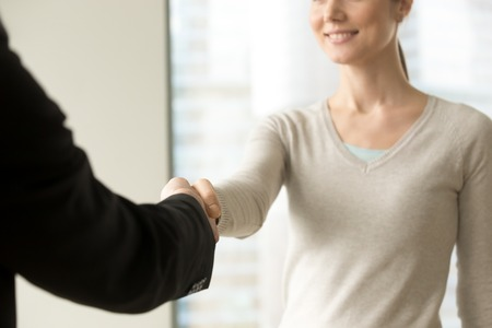 Smiling businesswoman shaking businessman hand standing in office, friendly welcome gesture, thanking for help, greeting new client, nice to meet you handclasp, focus on handshake, close up view Stockfoto