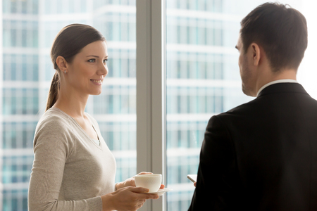 Attractive businesswoman listening to businessman talking at coffee break, happy lady holding cup and having informal conversation in office, smiling woman looking at colleague during discussion Reklamní fotografie