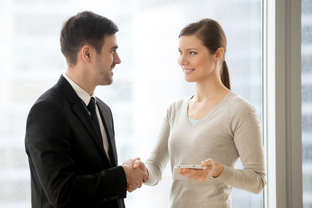 Happy cheerful businessman handshaking businesswoman with tablet, smiling boss hiring new smm manager for social media placement and online promotion, search engine optimization or digital marketing