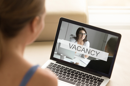 Young unemployed jobless woman looking for job, browsing web services searching work, reviewing available vacancies to submit resume and apply, close up view over the shoulder, focus on laptop screen Stock Photo - 84631340