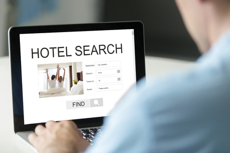 Businessman reserving room to stay on business trip or vacation abroad using online reservation booking service, website for worldwide fast hotel search concept, focus on laptop screen, close up