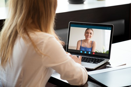 Two young women chatting online by making video call on laptop, using videoconferencing app for communication with distance friend, studying online course, virtual learning, close up rear view Stock Photo - 84744891