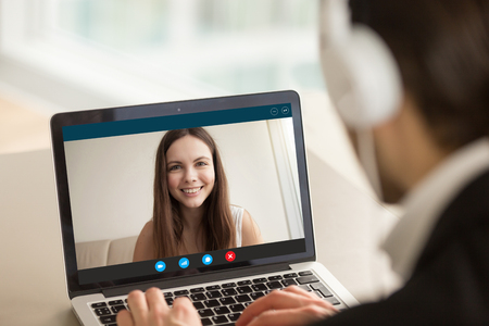 Smiling girl on videocall with guy, making video call to close foreign friend, talking by web camera, using virtual chat app online, long distance relationships, focus on screen, close up rear view Banco de Imagens