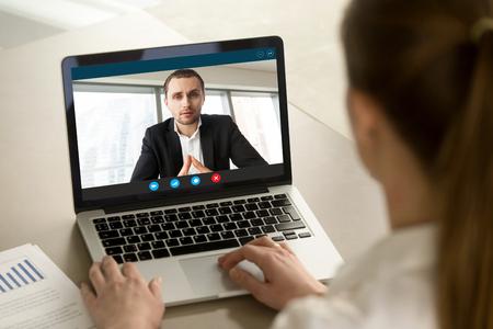Empresaria llamando a empresario en línea por video chat aplicación informática, los socios de negociación en línea en la reunión virtual, empleado de informes a jefe de negocio corriendo de forma remota, close up vista trasera