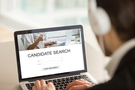 Employer searching candidates for part or full time job on internet web service, headhunter using laptop, looking for experienced professionals, choosing best staff, find resumes, close up rear view Stock Photo - 84744902