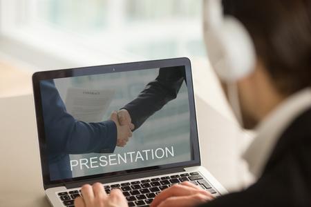 Zakenman in hoofdtelefoon met behulp van pc, kijken naar audio video computer zakelijke presentatie, kijken naar laptop scherm, kantoor werker voorbereiden diavoorstelling over opstart bedrijf, close-up achteraanzicht