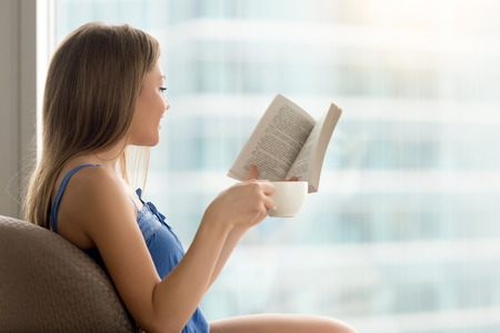 Young casual woman sitting in chair, reading interesting paper book, and drinking coffee. Lady resting at comfort home with favorite book in hand, enjoying good literature, relaxing in cafe on weekend Stock fotó