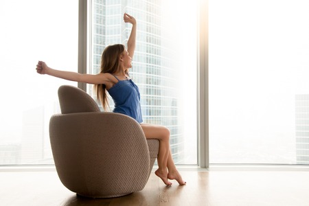 Young positive woman sitting and stretching in armchair near big bright window in hotel room. Relaxed lady feeling good in morning at home, enjoying start of new wonderful vacation day after waking up Stockfoto