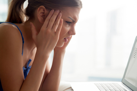 Stressed young woman feeling sharp pain in temples, suffering from headache, migraine after working on laptop. Worried lady reading e-mail with bad news, tired and nervous from too much computer work Stock Photo