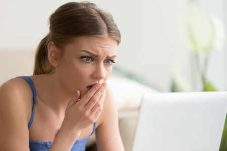 terrified woman: Upset young woman looking on laptop screen with fear. Lady with worried face watching horror movie, reading sad e-mail message, shocked of bad news in Internet, surprised with TV-show plot scary twist Stock Photo