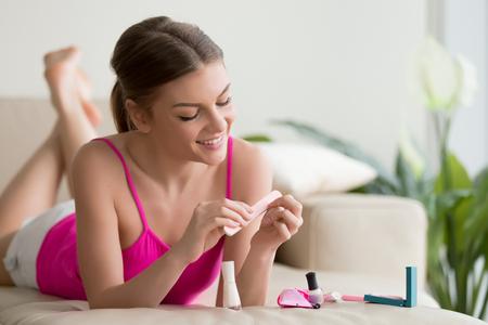 魅力的な笑顔若い女性はソファの上に横たわっている間爪のバッファーで爪を磨きます。自宅で安静時、週末楽しんで新しい化粧品を使用して幸せ