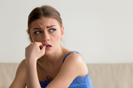 Portrait de tête d'une jeune femme inquiète se ronger les ongles et regarder de côté avec peur. Dame effrayée qui pense aux problèmes, a peur des difficultés, est nerveuse à cause de la mauvaise relation avec son petit ami Banque d'images - 85058121