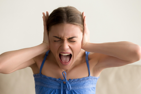 Portrait of stressed woman closing ears with hands and screaming with closed eyes. Hysterical lady feeling nervous breakdown, psychological problems, mood swing, fatigue and exhaustion, depression Stock Photo