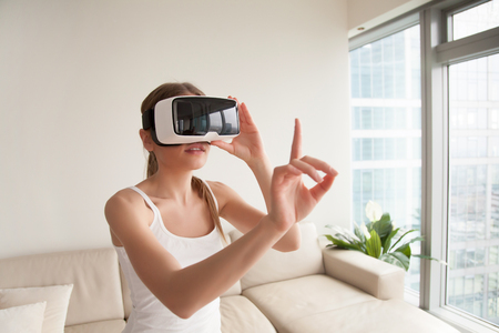 Woman in virtual reality glasses touching objects in augmented reality, interacting with 3d simulation. Lady selecting app menu items, working in virtual interface, wearing VR headset helmet at home
